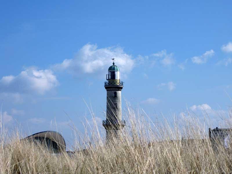 Blick vom Strand der Ostsee auf den Leuchtturm in Warnemünde.